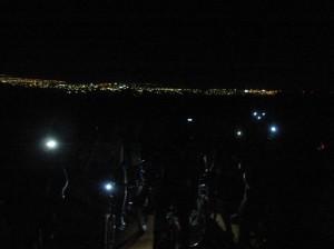 Faróis da bike confundem-se com as luzes da cidade. Que visual.