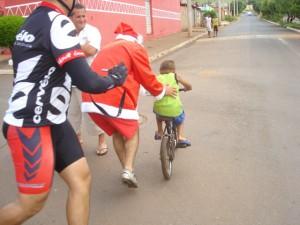 Papai Noel dando um empurrãozinho no garoto